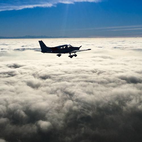 Ein Piper-Sportflugzeug fliegt über den Wolken