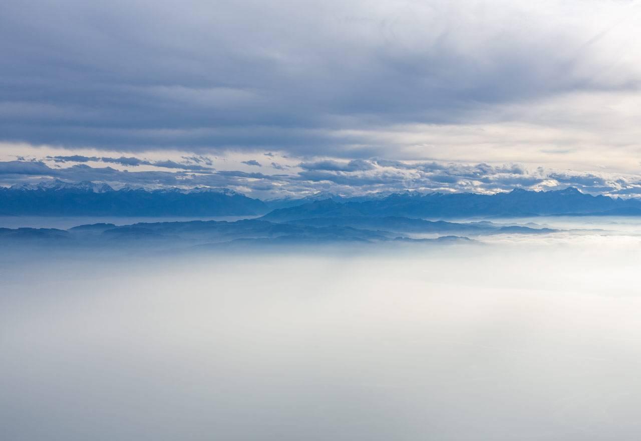 Blick auf Bodensee und Rheintal beim herbstlichen Flug zwischen Wolkendecke und Nebel